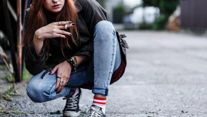 Teen smoking and crouching down