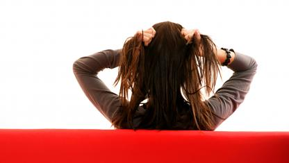 woman sitting on couch pulling on hair