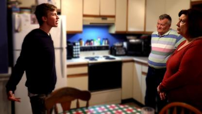 A teen boy has a discussion with his parents.