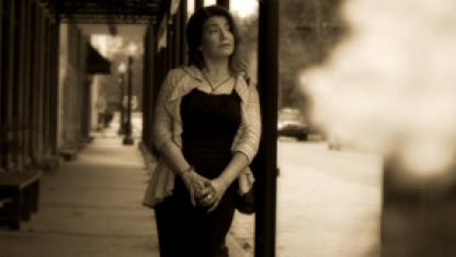 Photo of a lady in front of a store.