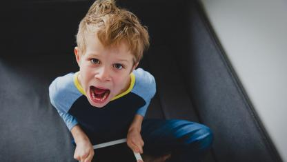 Young boy with mouth open screaming