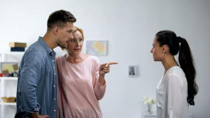 Woman talking to man pointing at another woman