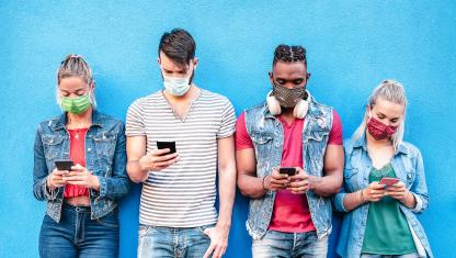 Young men and women wearing masks and looking down and cell phones