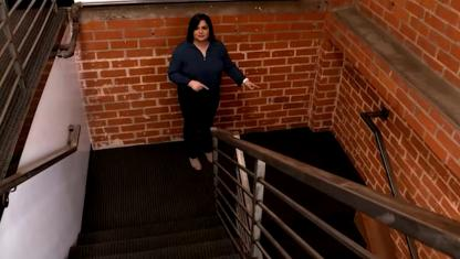 Photo of a girl standing on a staircase.