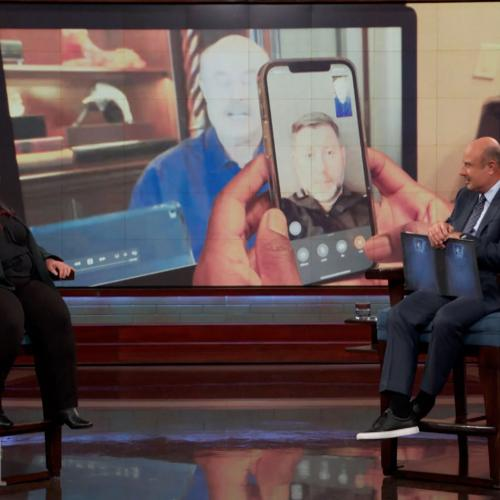 Dr. Phil speaking to a female guest onstage.