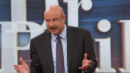 Dr. Phil onstage speaking to the audience after the taping