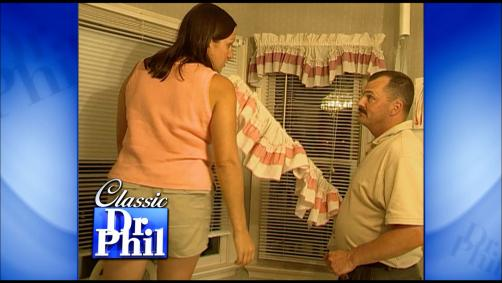 A man and wife hanging curtains