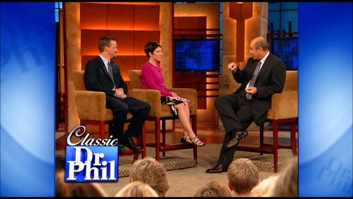 Dr. Phil speaking to a husband and wife on stage.